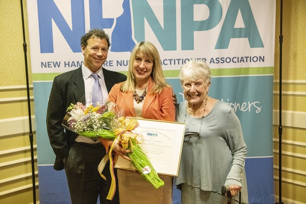 Christine Ferreri 2019 NP of the Year, stands with her award and flowers between her husband and mother.